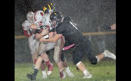 HCHS senior Nick Foss secures the football with both arms during a third-quarter downpour as two Winterset players, including Casey Kleemeier (1), make the tackle. Foss rushed for 142 yards in the Cyclones' 7-6 victory.