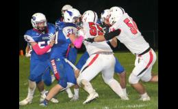 AHSTW senior Joey Goins (21) carries the fooball as Earlham's Chris Hipsley (55) and Grant Carter (54) look to make the tackle. (Photos by Kim Wegener)