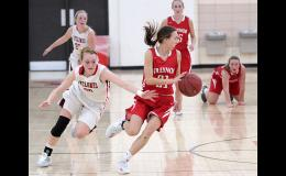 HCHS senior Lexi Larsen (left) has the ball stolen away by Treynor's Mandy Stogdill during Monday's first half.