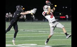 Harlan Community linebacker Jon Owens makes one of the Cyclones' three interceptions during Friday's 35-6 win at Carroll as Tiger receiver Jace Pettitt reaches back for the underthrown pass.