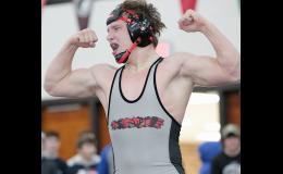 HARD-FOUGHT TITLE -- Harlan Community senior Jacob Wingert celebrates with a flex after defeating Urbandale's Austin Lamm 9-8 in the 170-pound championship match of the Dan Hill Invitational on Saturday. Wingert is the Cyclones' first Dan Hill champion in three years.