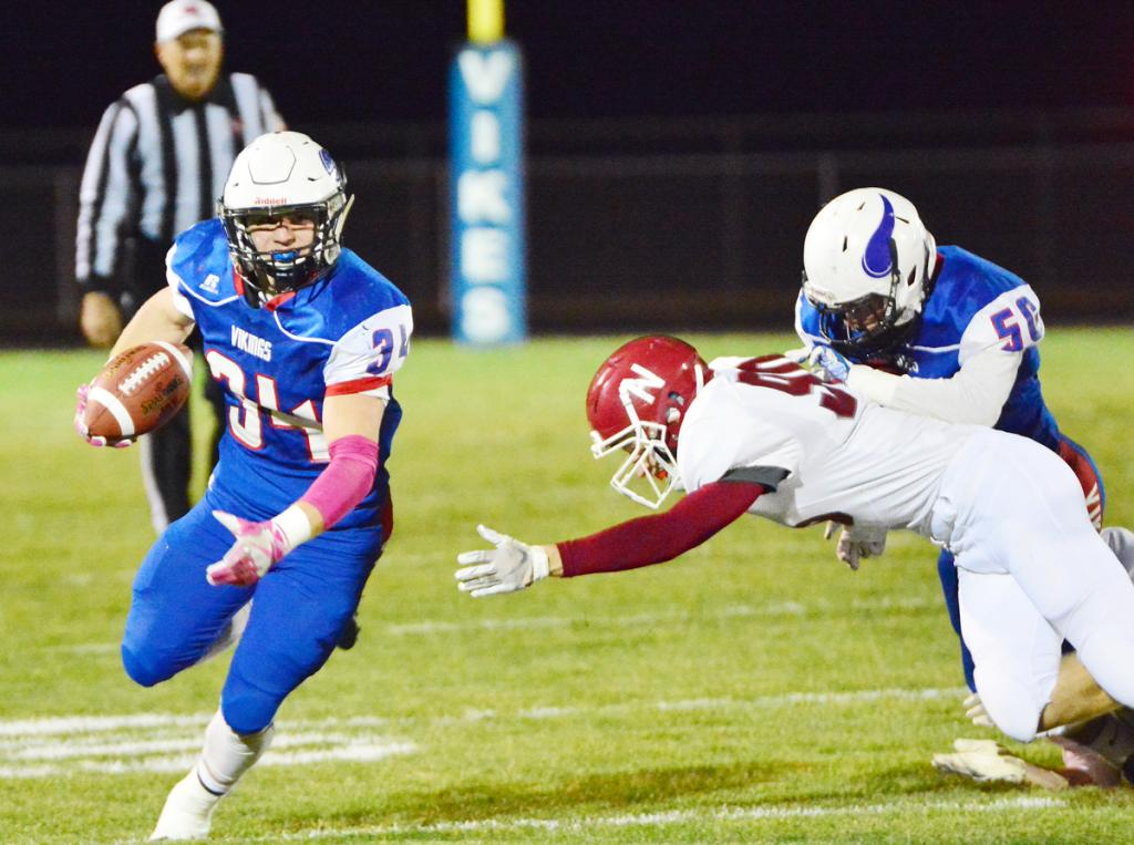 Viking senior Gabe Pauley (left) scores a 56-yard touchdown on the first play of the game, taking advantage of a block by Seth Kiesel (50) on a Newman Catholic tackler.