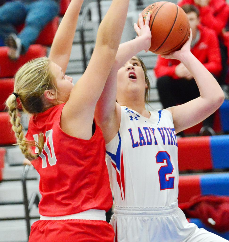 AHSTW's Kailey Jones (2) looks toward the basket as she is guarded by Treynor's Sydni Huisman.