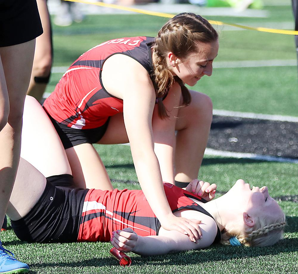 HCHS senior Greichaly Kaster (bottom) is greeted by teammate Abby Alberti after anchoring the Cyclone 4x800 relay to a second-place finish and an automatic state qualifier berth.