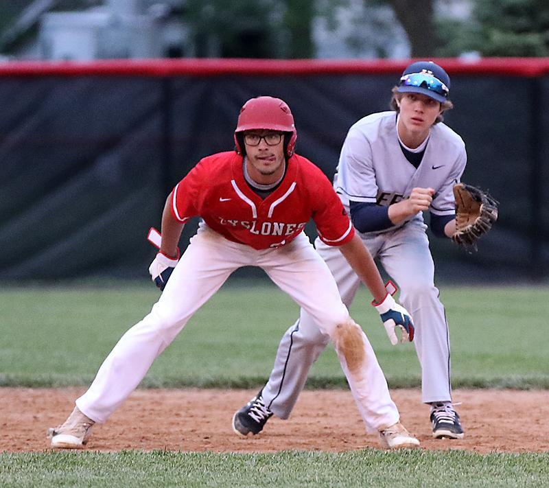Bishop Heelan shortstop Sean Schaefer (right) tries to shorten the lead of HCHS senior Ben Muenchrath off second base. (Photos by Mike Oeffner)