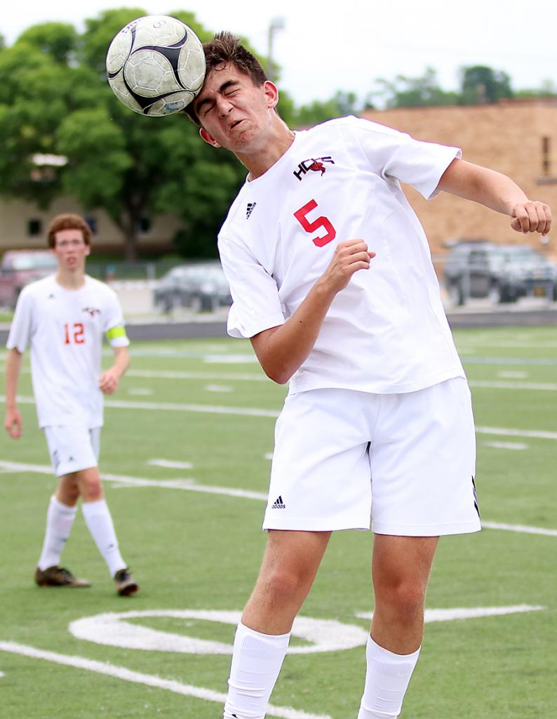 Cyclone junior Colton Barnes heads the ball across the midfield area against Lewis Central.