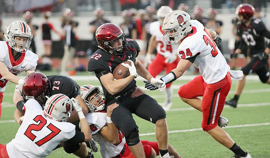 ADM running back Nick Bradshaw (22) is tackled by HCHS sophomore Brenden Bartley (36) and Jon Owens.
