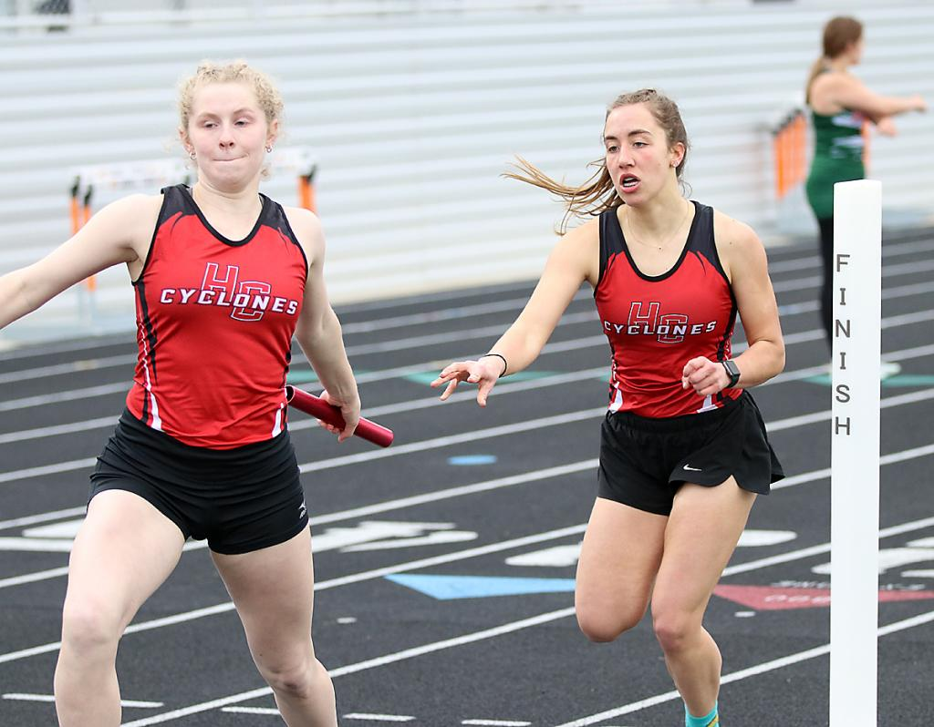 Cyclone senior Brecken Van Baale (left) takes a handoff from Kaia Bieker as part of the winning 4x800 meter relay. (Photos by Mike Oeffner)