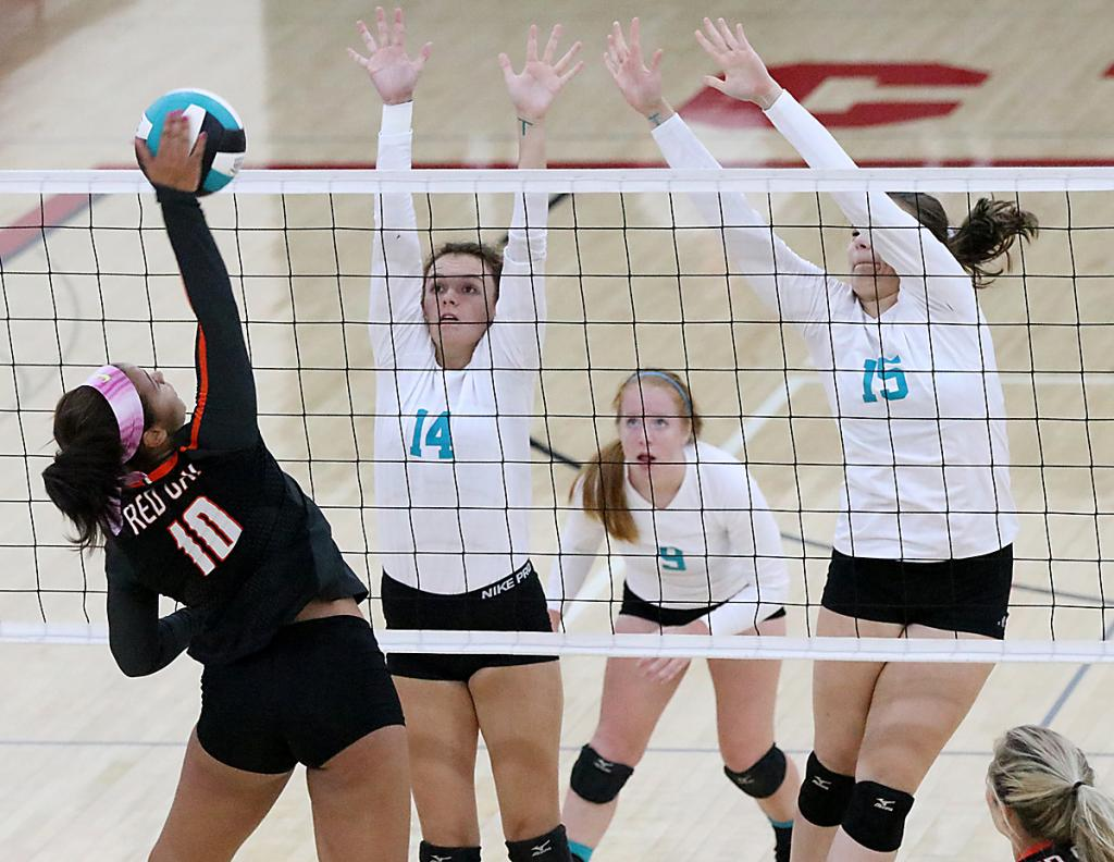 Red Oak's Chloe Johnson (10) goes on the attack against HCHS blockers Anna Ahrenholtz (14) and Lauren Andersen (15) as Kara Weis looks on. (Photos by Mike Oeffner)