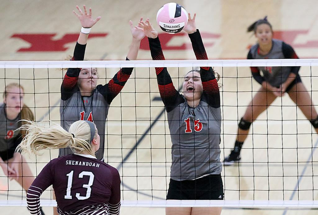 HCHS sophomore Lauren Andersen (15) and senior Anna Ahrenholtz rise up for a block against Shenandoah's Logan Hughes during Tuesday night's Hawkeye Ten match. Also pictured for HCHS are Kara Weis (left) and Hayley Hopkins.