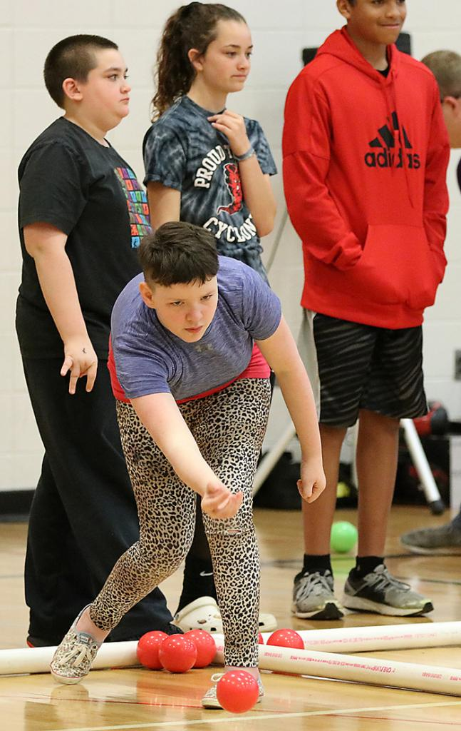 Jasmine Powley rolls the ball as, left-right, Tristan Harvey, Ellie Ineson and Lokahi Smith wait their turn during last week's Harlan Community School District Special Olympics Bocce Ball Tournament at the Primary School gym. (Photos by Mike Oeffner)