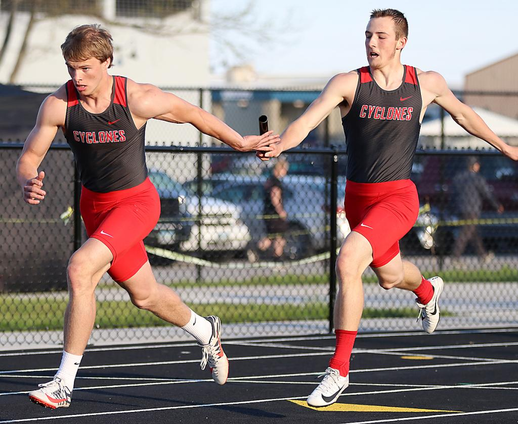 HCHS senior Eli Boldan takes a handoff from Johnathan Monson in the 4x200 relay before anchoring the Cyclones to a gold medal Friday night in Carroll.