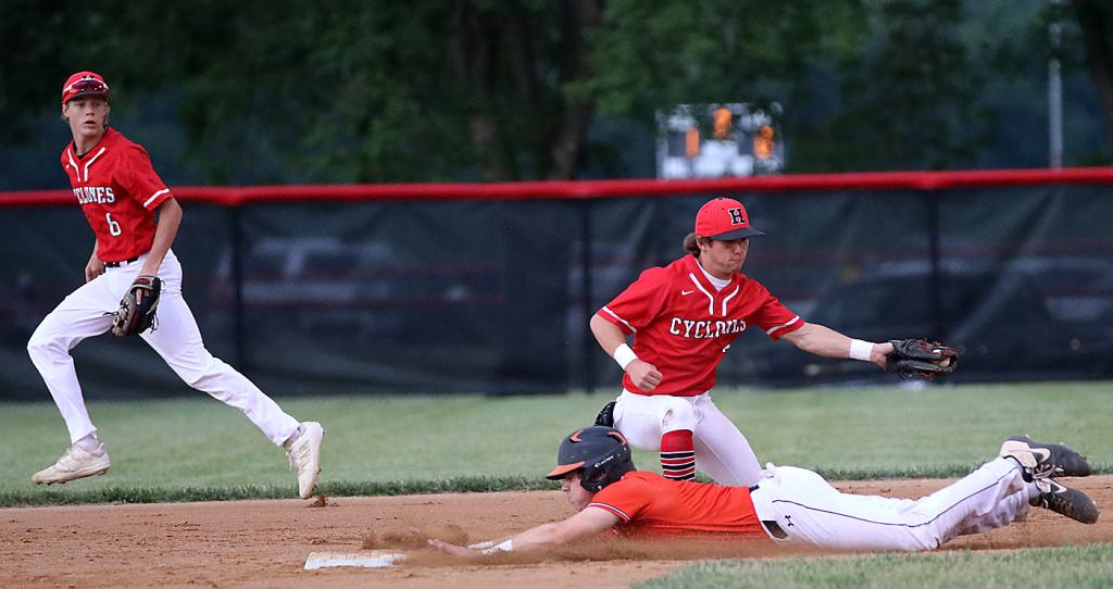 Carroll's Cade Schable slides head-first into second with a stolen base just ahead of the tag by HCHS shortstop Joey Moser as second baseman Cade Sears backs up the throw.
