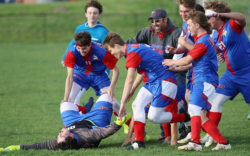 Goalie Lucas Young falls to the ground as teammates and coaches celebrate the Vikings' 2-1 victory. (Photos by Mike Oeffner)