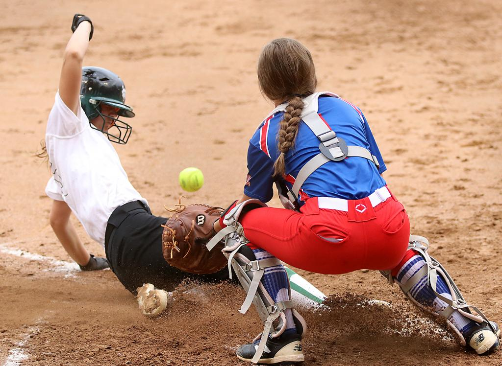IKM-Manning's Jessica Christensen slides home safely with the Wolves' lone run Thursday, beating the throw to AHSTW catcher Rylie Knop at the plate.