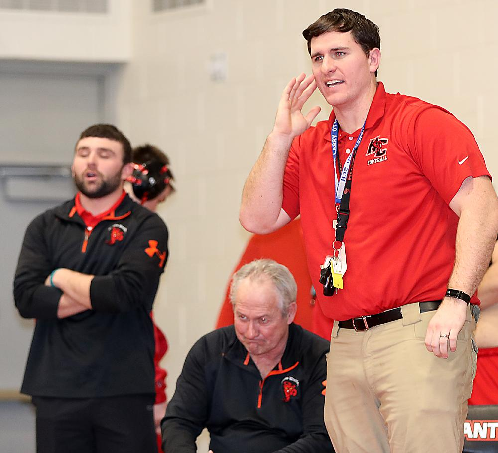 HCHS coaches Matt Hoch (right), John Murtaugh (seated) and Broghan Kelly show their emotions as the Cyclones take on Creston/O-M in Tuesday's last dual of the night.