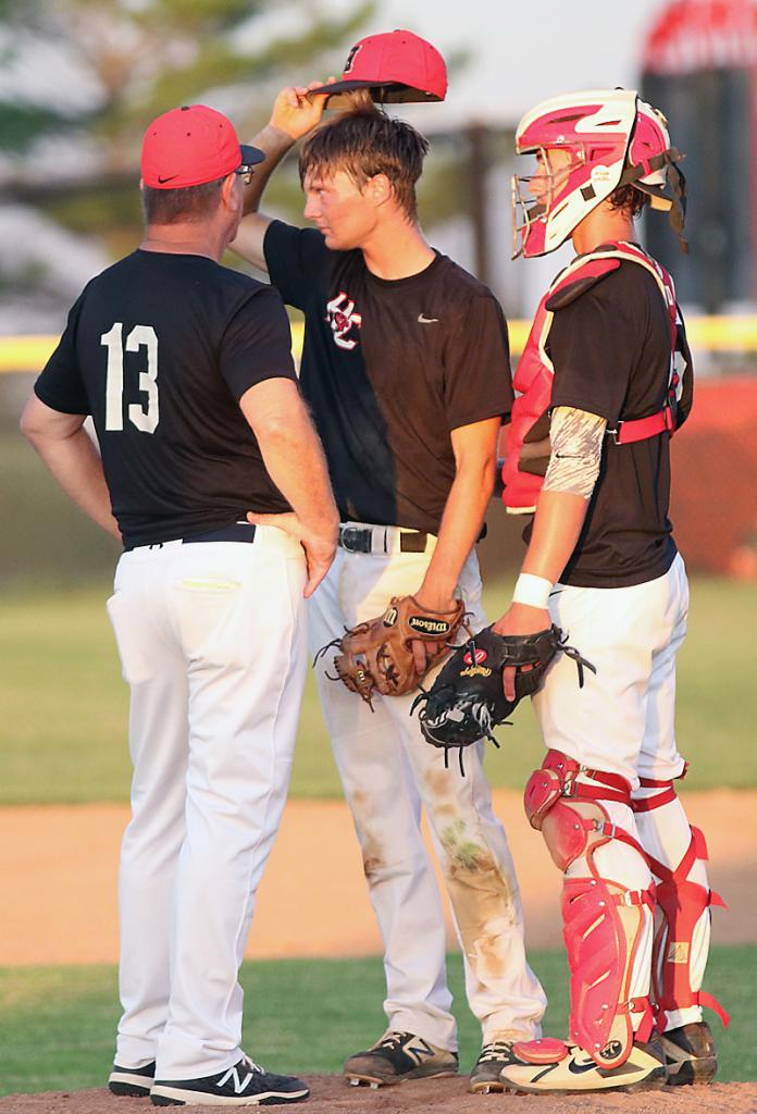 Cyclone head coach Steve Daeges (13) talks with the battery of Connor Bruck and Brenden Bartley during Dallas Center-Grimes' eight-run sixth inning.