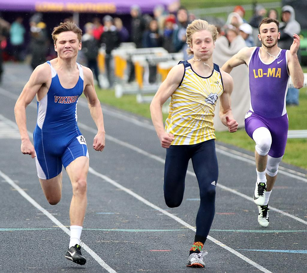 AHSTW senior Drake Partridge (left) and Riverside's Valentin Andrusyshyn near the finish line in the 100-meter dash at Tuesday's WIC Track Meet. Partridge won in a photo finish - both runners were clocked at 11.32 - and finished the night with four gold medals.