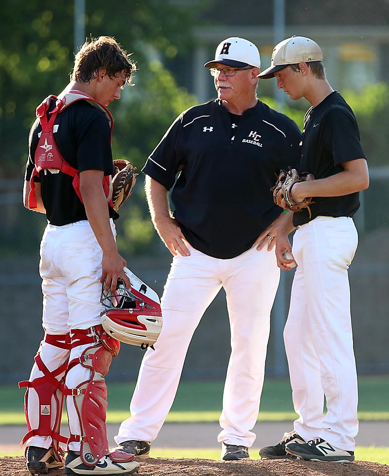 Coach Daeges talks with pitcher Connor Bruck and catcher Brenden Bartley during a 2019 game.
