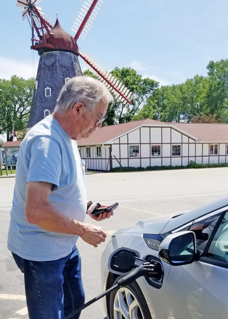 Bob Mortensen of Elk Horn recharges his hybrid vehicle at the Danish Windmill's new ChargePoint station in Elk Horn.  (Photo contributed)