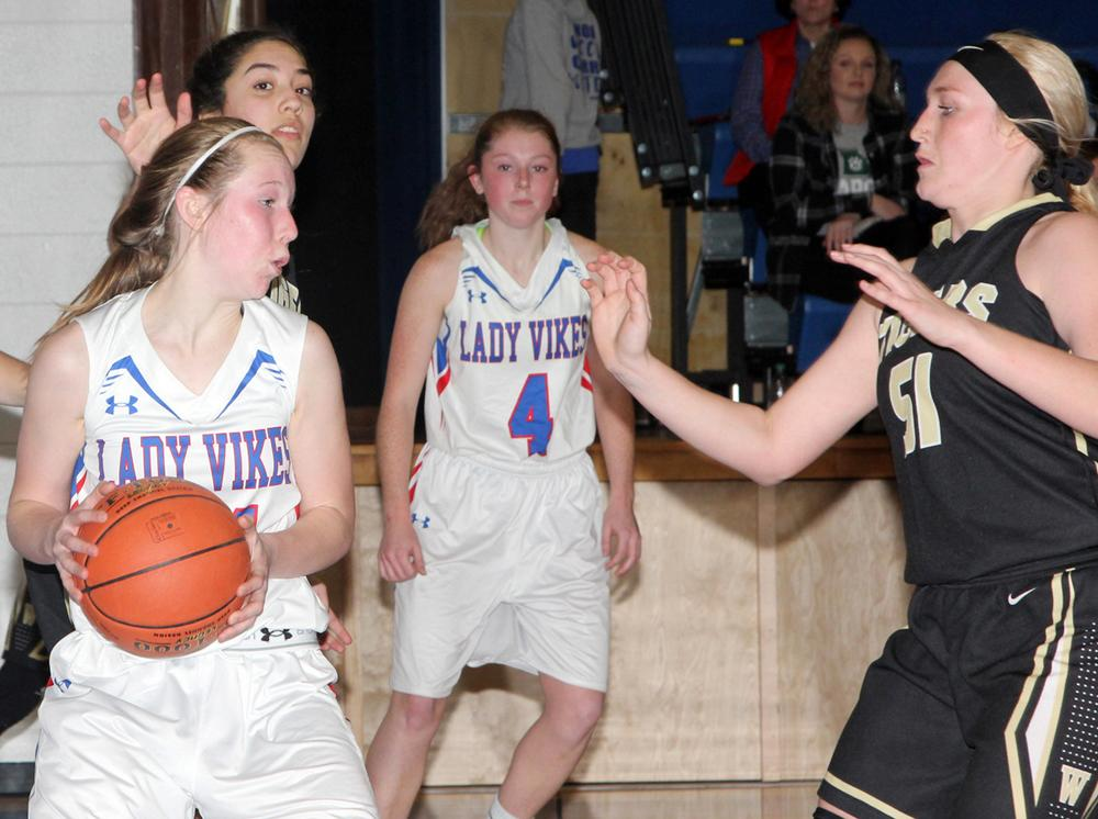 AHSTW sophomore Claire Denning (left) is guarded by Woodbine's Ramie Vaughn (51) as Katie Anzalone (4) looks on.