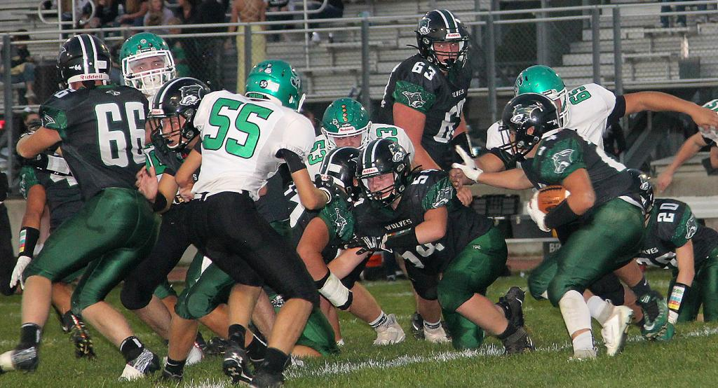 IKM-Manning's Drew Doyel (right) carries the football with blocking help from Tanner Crawford (54), Brody Swearingen (66), Max Nielsen (63) and others. (Photo by Kim Wegener)