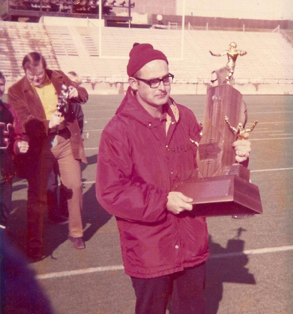 Former Harlan Community head football coach Terry Eagen holds the Cyclones' first-ever state football championship trophy following a 14-12 win over Cedar Rapids Regis at Kinnick Stadium in 1972. Pictured in the background is then-assistant coach Curt Bladt, who would lead HCHS to 11 more state titles in 42 years as the head coach. (Photo contributed)