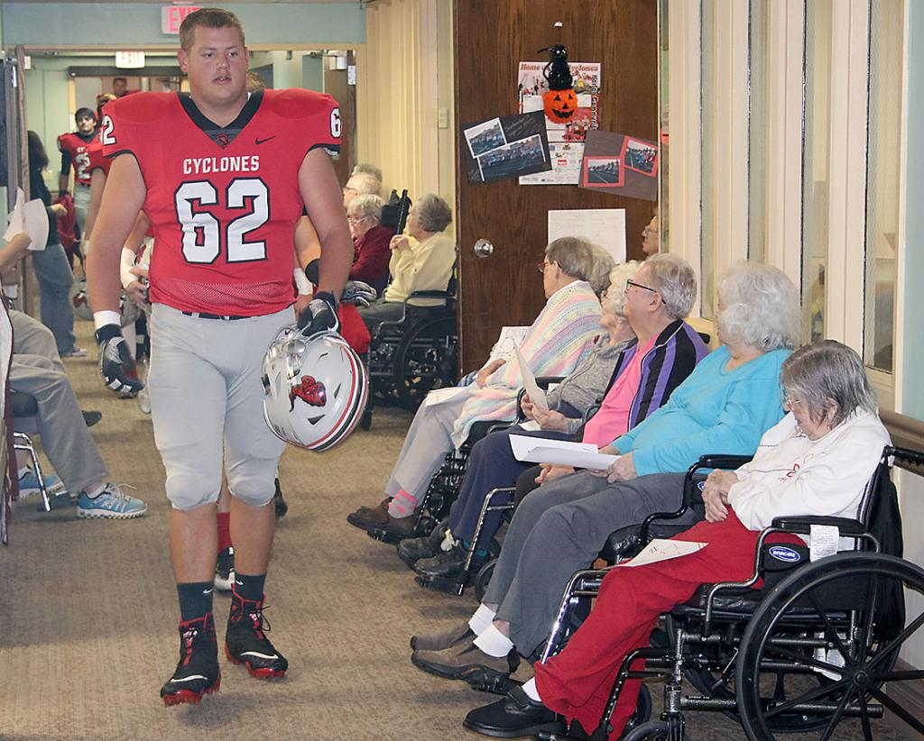 HCHS senior Derec Weyer (62) leads the charge of Cyclone players through the hallway at Elm Crest.