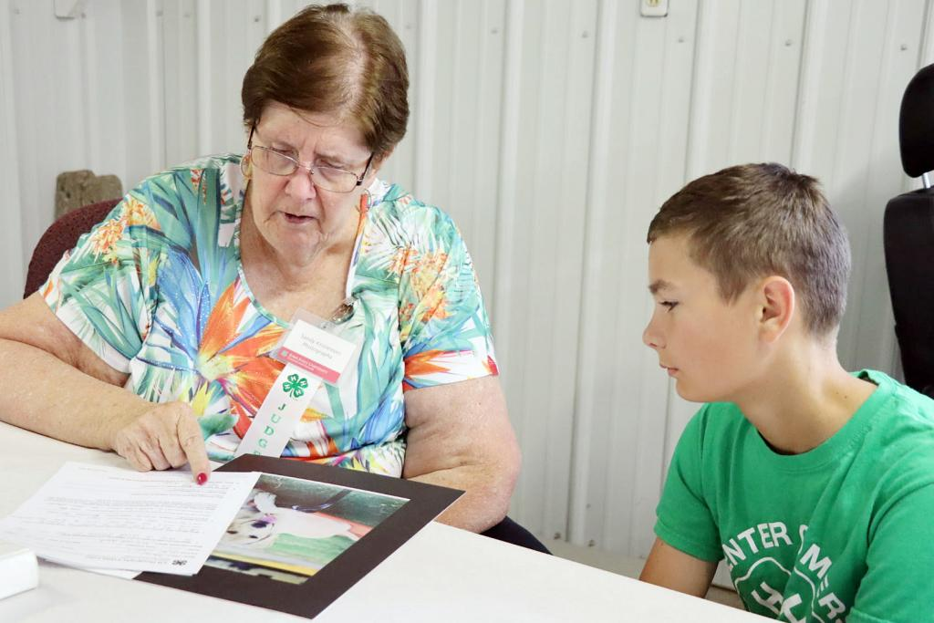 The Shelby County Fair kicked off this week at the fairgrounds in Harlan.  A full schedule is planned for the upcoming weekend.  Here, photography judge Sandy Kristensen talked with Grant Petersen about his project at the 4-H Static Exhibit judging Tuesday, July 13.