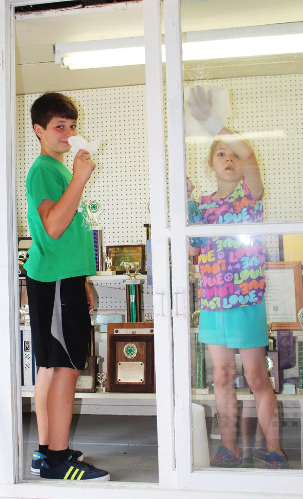 Colton Schleimer and Edie Mae Kaufmann clean the 4-H trophy display case.