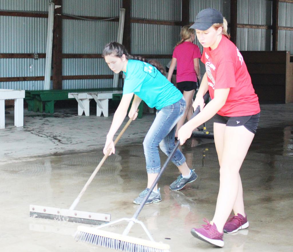 Shaylee Yates (left) and Cameron Springman push water out of the commercial building after cleaning the floor.