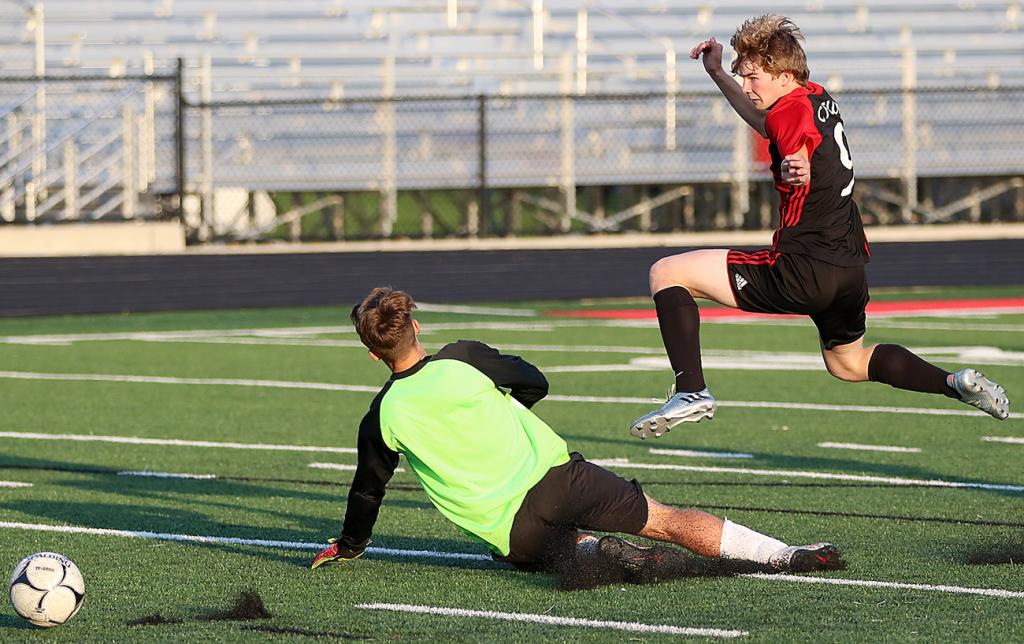 HCHS junior Jordan Fink (right) scores his second goal of the game past a sliding Creston goalie, Derek Paup, during the Cyclones' 6-0 win at Merrill Field on Monday. HCHS clinched a share of the Hawkeye Ten title. (Photos by Mike Oeffner)