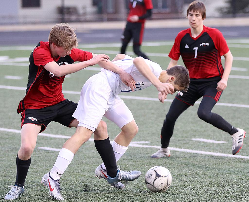HCHS junior Jordan Fink (left) battles a Titan player for the ball as Dalton Gross (7) looks on. Fink scored three goals for his first varsity hat trick. (Photos by Mike Oeffner)