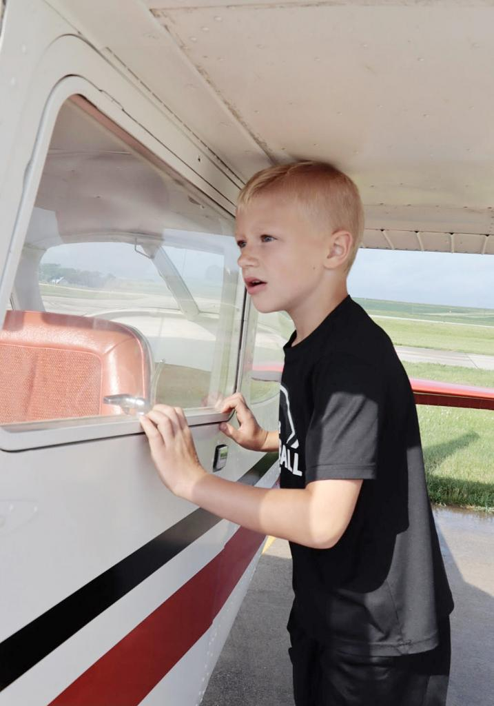 Nolan Havens peers into one of the planes on display at the 75th annual Flight Breakfast at Rushenberg Field.