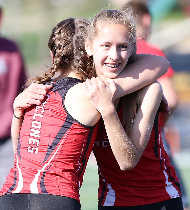 ON TO STATE -- HCHS sophomore Liv Freund (right) hugs Abby Alberti after they helped the Cyclones qualify for state in the 4x800 relay. (Photos by Mike Oeffner)