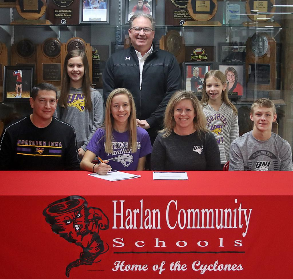 HCHS senior Liv Freund signed a national letter of intent on Dec. 21 to join the women's track and field program at the University of Northern Iowa. Front row: Liv Freund (second from left) is seated next to her parents, Matt and Laura Freund, and younger brother Luke. Back row, L-R: Ava Freund (younger sister), HCHS girls track coach Doug Renkly, Sophia Freund (younger sister).