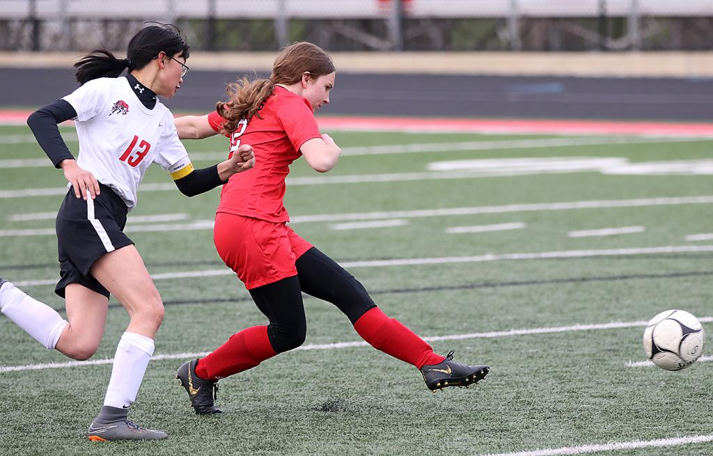 Cyclone freshman Hailey Good attempts a shot as Conner Allender (13) defends for the Rams. Good scored her first two varsity goals.
