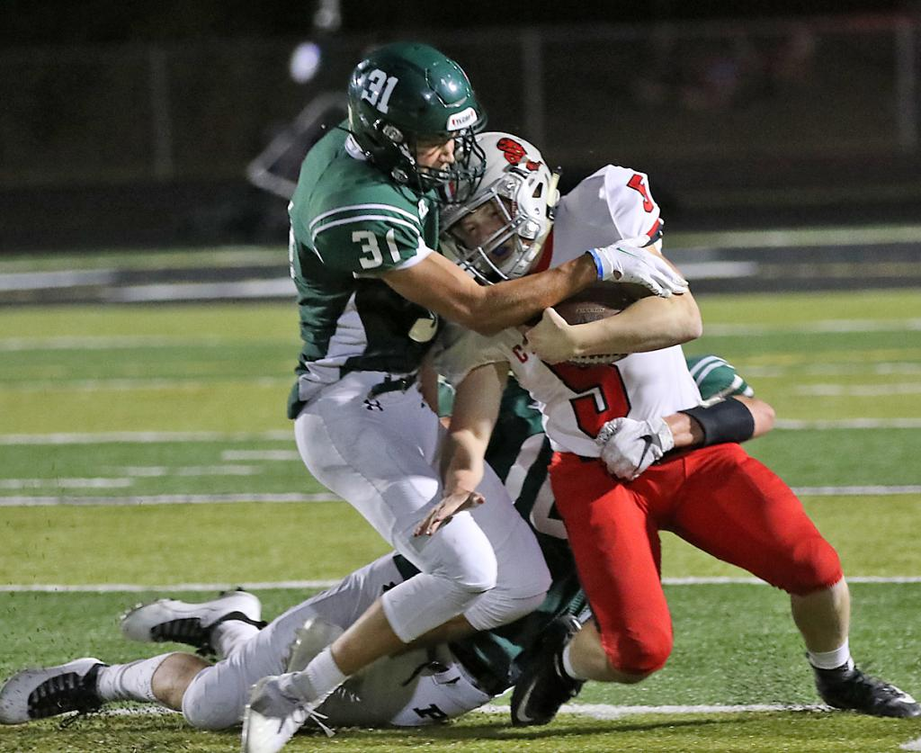 HCHS tailback Mason Griffith fights for yardage as Pella's Reece Thoreson and a teammate make the tackle.