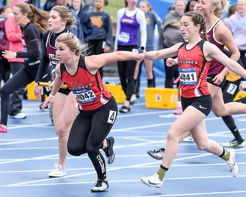 Harlan Community junior Abby Alberti (right) hands the baton to senior anchor Chloe Hansen in the Drake Relays' 4x100 relay Saturday morning. HCHS clocked a season-best time of 51.57 seconds and finished 34th out of 96 qualifiers, with freshmen Savanna Musich and Delaney Wegner running the first two legs of the race. (Photo courtesy of Scott Vicker)