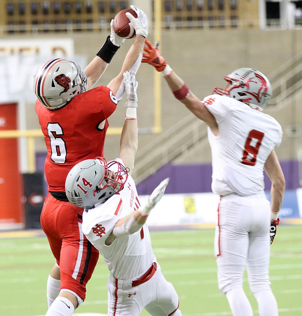 Harlan Community sophomore receiver Aidan Hall (6) high-points a reception between North Scott's Oliver Hughes (8) and Hunter Davenport that turned into a 58-yard touchdown with :01 left in the first half of Thursday's Class 3A state championship game at the UNI-Dome. It was the only Cyclone score of the night as they suffered their first loss of the season, 30-6.