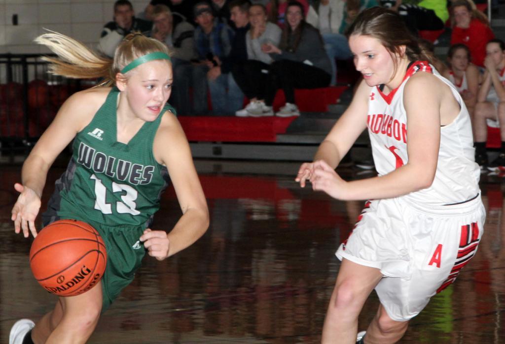 Wolves' sophomore Nicole Hanson (13) drives toward the hoop. (Photos by Kim Wegener)