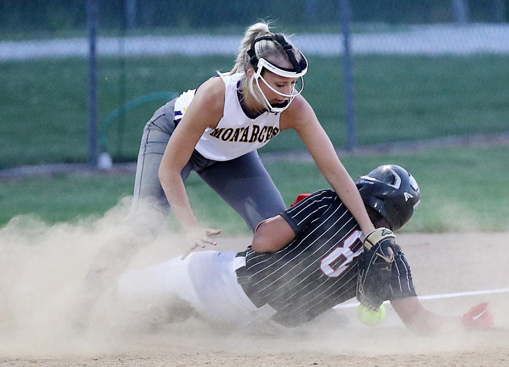 HCHS junior Kate Heithoff (8) slides in safely at third base as the ball gets away from Monarch third baseman Kira Langenfeld.