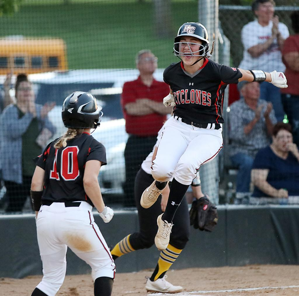 Harlan Community freshman Kate Heithoff leaps in celebration after scoring the Cyclones' third run on Morgan Schaben's fifth-inning two-run double against Atlantic Monday night. Tianna Kasperbauer (10) also scored on the hit as HCHS beat the Trojans 3-0 in Harlan. (Photos by Mike Oeffner)