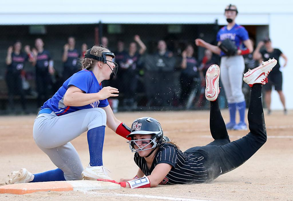 HCHS junior Kate Heithoff gets back to the bag safely ahead of the tag attempt by AHSTW first baseman Ally Meyers.