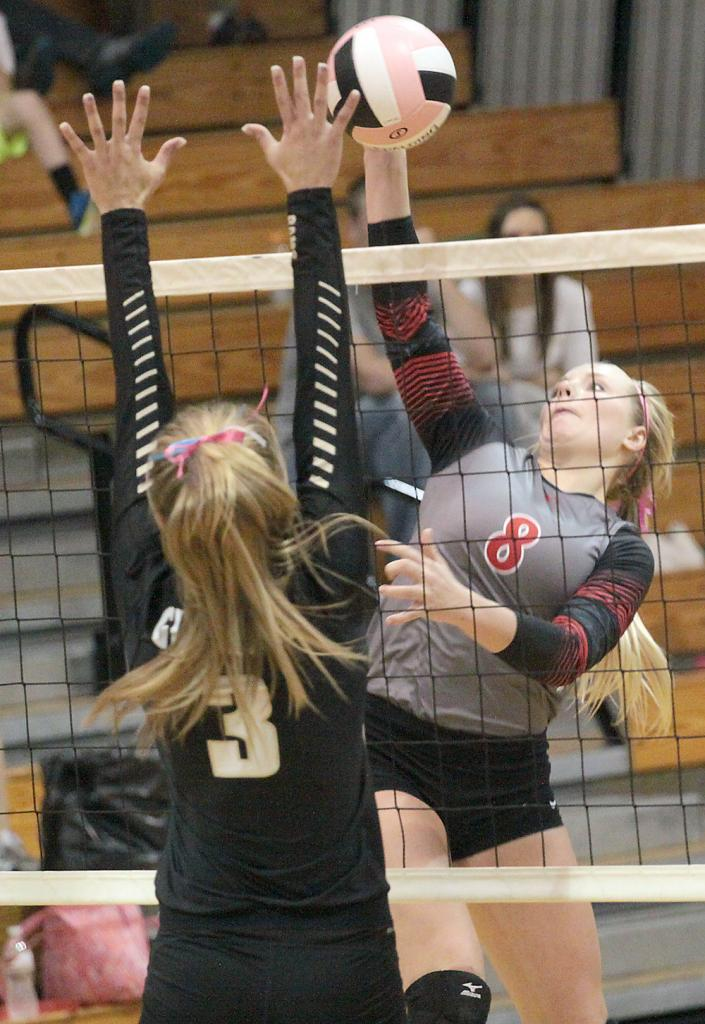 Sophomore Lexie Holloway (8) tries for a kill over Glenwood's Kali Mumm. (Photos by Mike Oeffner)