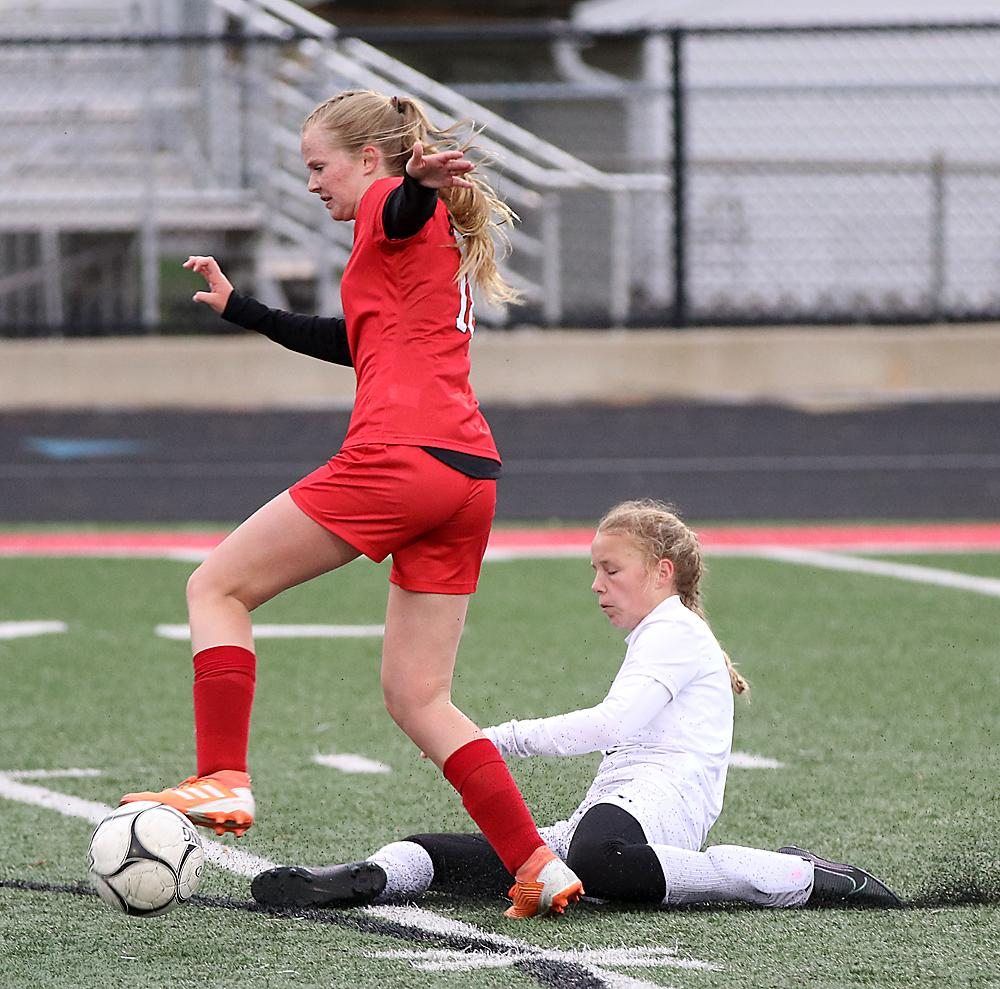 Samantha Ineson of HCHS (left) avoids the sliding Whitlee Auen of Denison to maintain control of the ball.