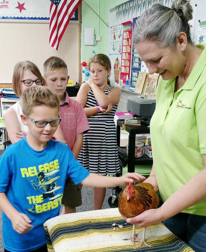 Students at IKM-Manning Elementary learn how to care for chickens in a chicken life cycle lesson. They learned what chickens eat and when chickens are mature enough to begin laying eggs.  (Photo contributed)