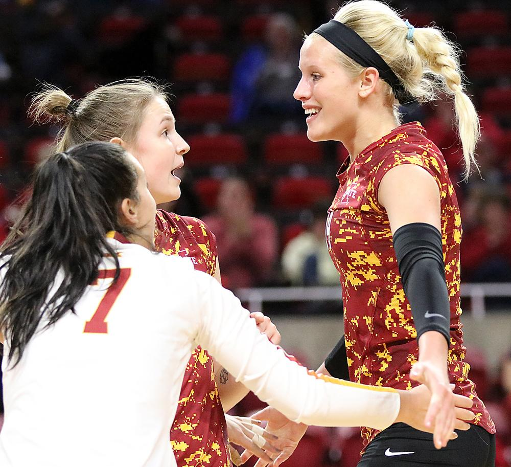 Jess Schaben (right) celebrates an Iowa State point with setter Piper Mauck and libero Izzy Enna (7) during the team's win over West Virginia. Schaben finished the four-set match with 22 kills and 18 digs.