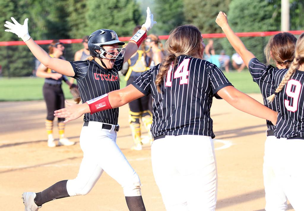 HCHS junior Jordan Heese (left) celebrates with teammates, including Emily Brouse (14), after hitting a game-tying home run in the sixth inning of Tuesday's home game vs. Atlantic. The Trojans prevailed 11-7 in nine innings.