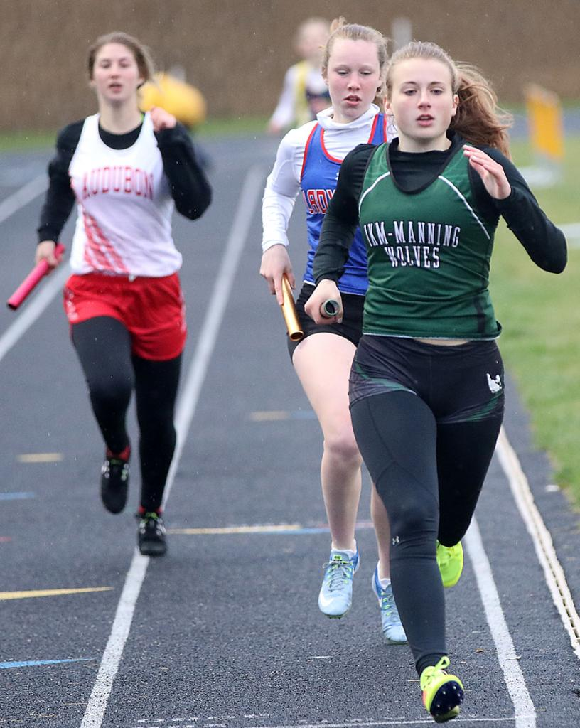 Kamryn Lesle of IKM-M runs just ahead of AHSTW's Claire Denning on the 400 leg of the distance medley relay.